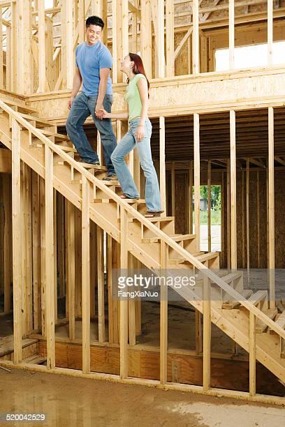 Jeune couple tenant les mains sur les escaliers de nouvelle maison construction