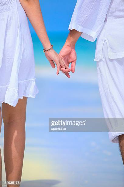 Young couple holding hands on turquoise white sand tropical beach