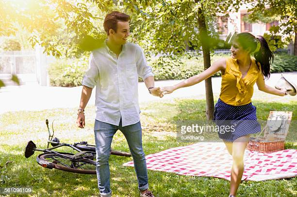 Young couple holding hands running