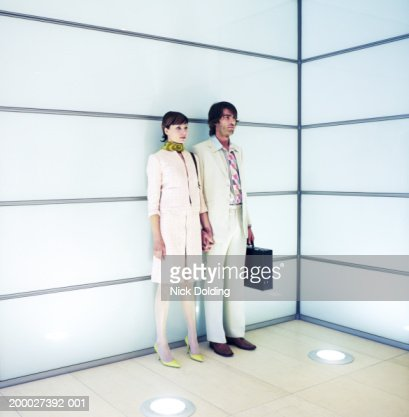 Young couple holding hands, standing against wall : Stock Photo