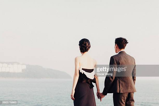 Young couple holding hands standing by sea