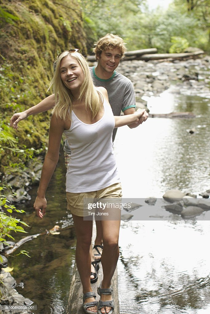 Young couple holding hands, walking by river
