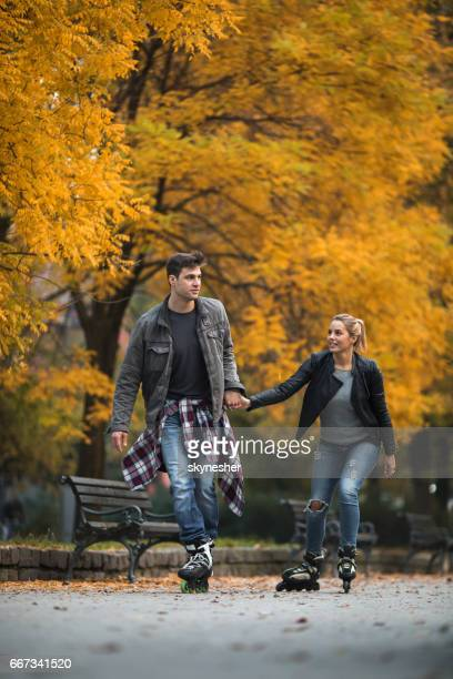 Young couple holding hands while roller skating in autumn.
