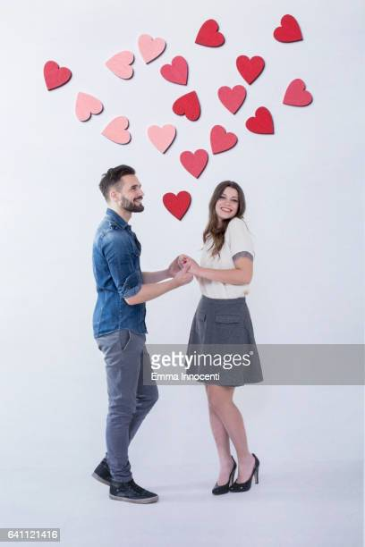 Young couple holding hands with hearts