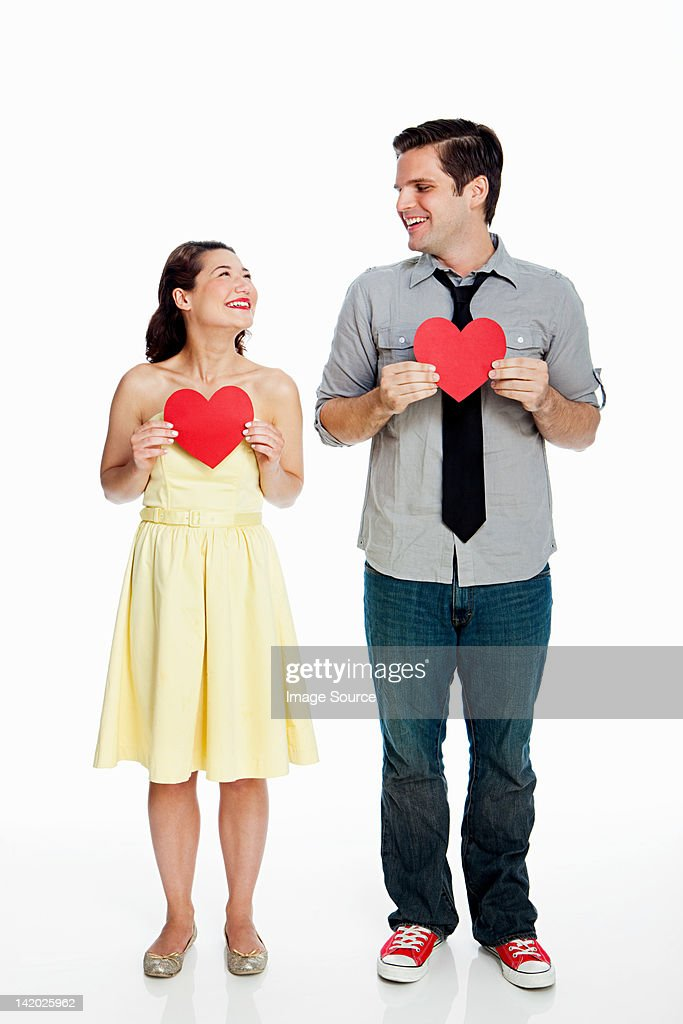 Young couple holding heart shapes against white background : Stock Photo