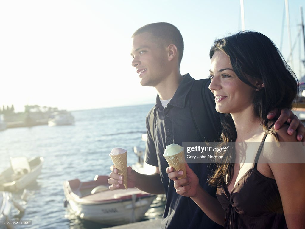 Young couple holding icecreams by sea, smiling : Stock Photo
