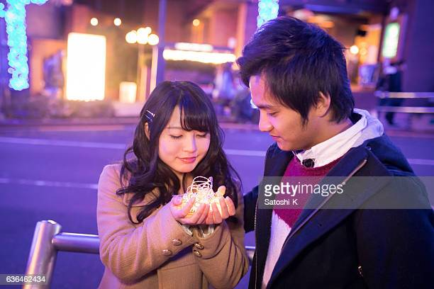 Young couple holding lights on hands