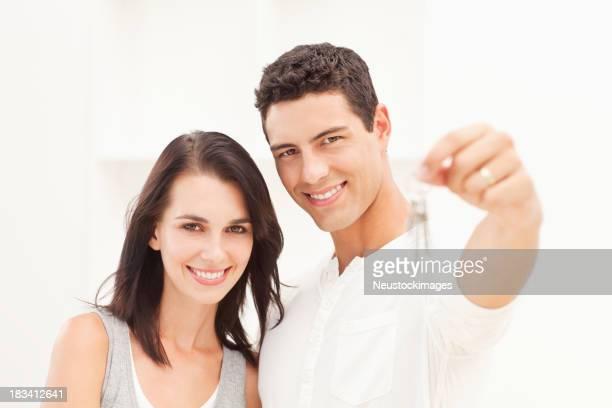 Casal Jovem segurando as chaves da casa nova