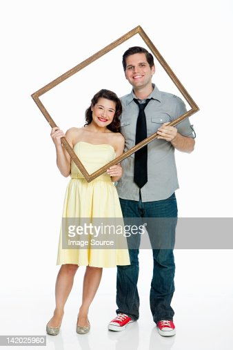 Young couple holding picture frame against white background : Stock Photo