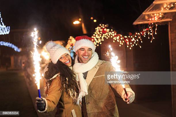 Young couple holding sparkling candles on street at night