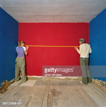 Young couple holding tape measure against wall, rear view