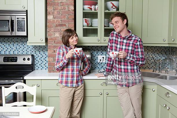 Young couple holding teacups in kitchen