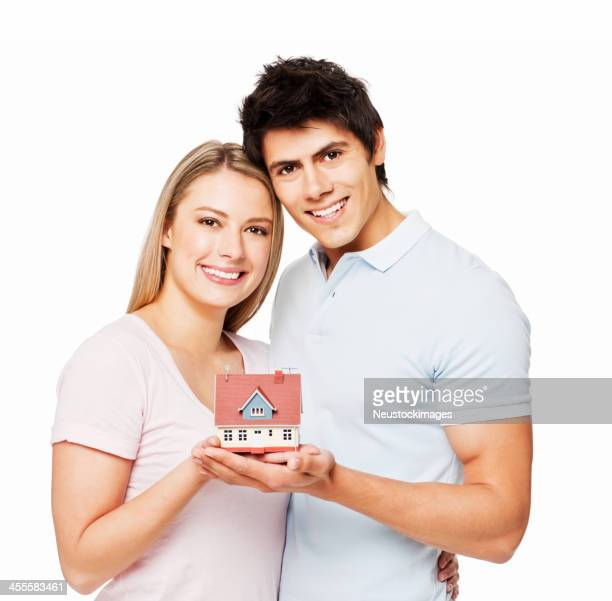 Young Couple Holding Up a Model Home - Isolated
