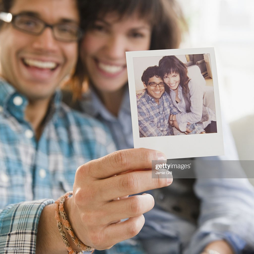 Young couple holding up picture of themselves : Stockfoto