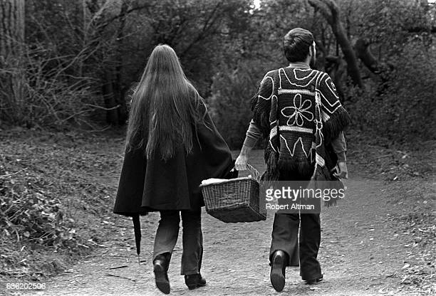 A young couple holds a picnic basket while walking through Golden Gate Park circa February 1969 in San Francisco California