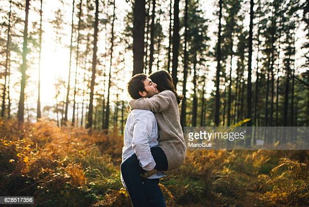 Young couple hugging at forest