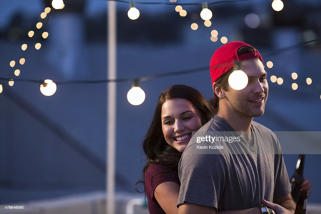 Young couple hugging at rooftop barbecue : Stock Photo