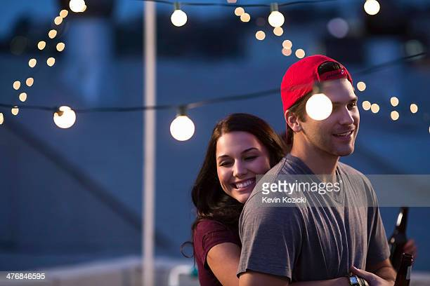 Young couple hugging at rooftop barbecue