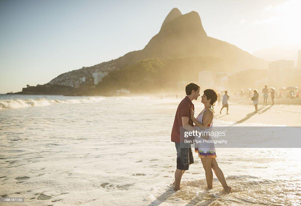 Young couple hugging at sunset, Ipanema Beach, Rio, Brazil