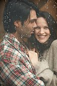Young couple hugging by window with rain running down