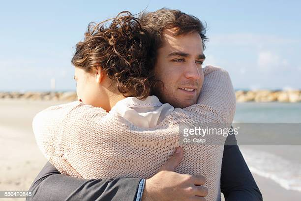 Young couple hugging each other on beach, Tel Aviv, Israel