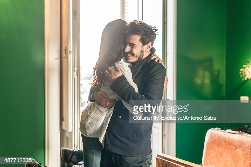 Young couple hugging in room