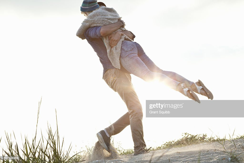 Young couple hugging on Bournemouth beach, Dorset, UK