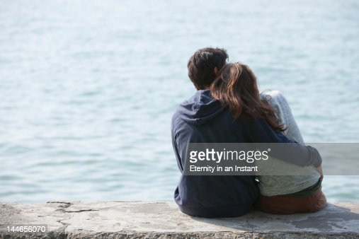 Young couple hugging outdoors by the sea : Foto de stock
