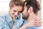 Close-up portrait of beautiful young couple hugging at home