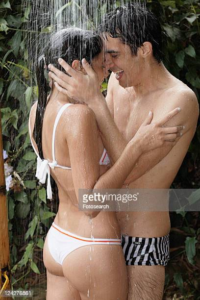 Young couple hugging under shower near plants