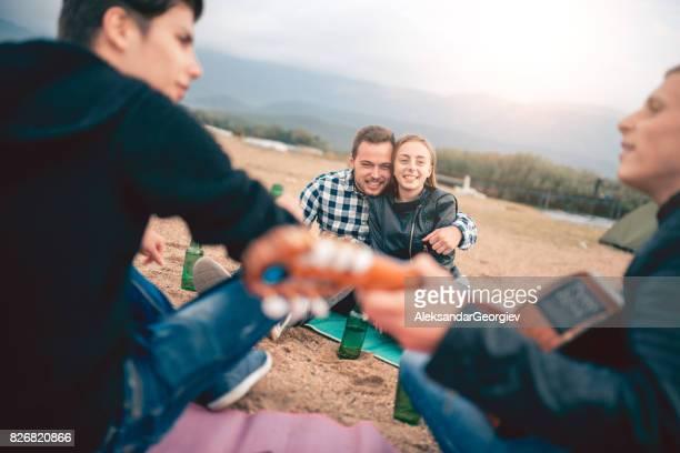 Jeune Couple caresses tandis que leurs amis jouer de la guitare sur la plage