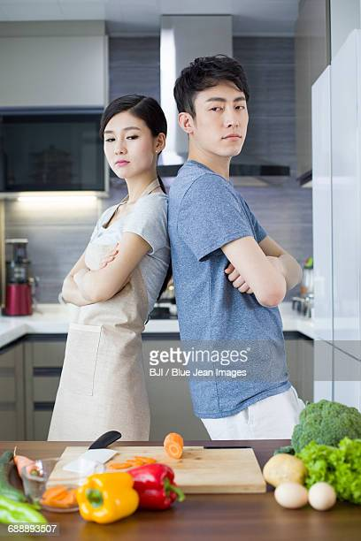 Young couple ignoring each other in kitchen