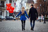 A young couple in a coat are holding a balloons heart in the city street. Valentine's Day.