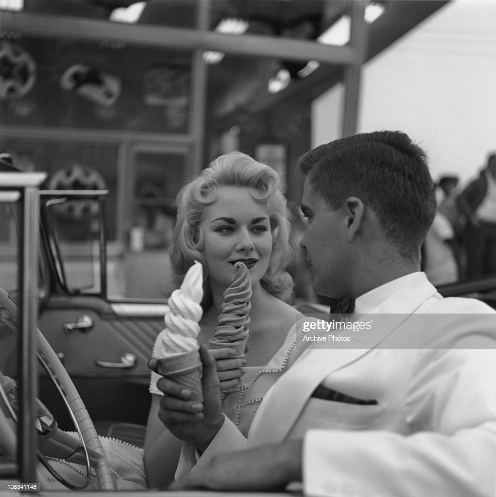 A young couple in a convertible gaze at each-other, while holding large Carvel ice cream cones, USA, circa 1955.
