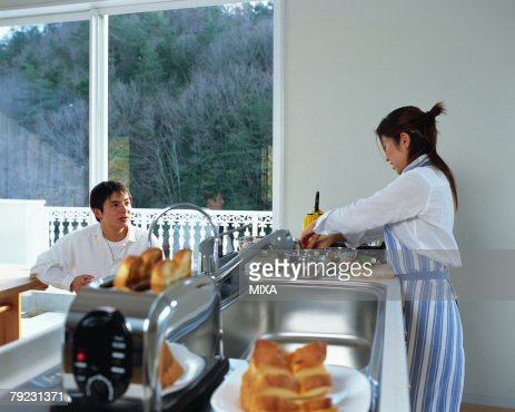 A young couple in a kitchen : Stock Photo