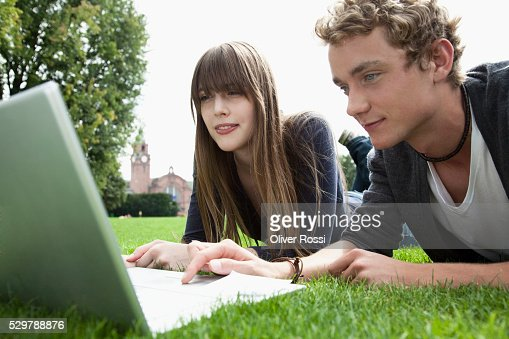 Young couple in a park using a laptop : Foto stock