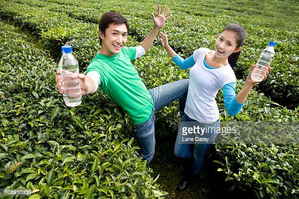 Young Couple in a Tea Field With Water Bottles