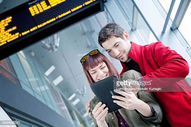 Young couple in airport building using digital tablet