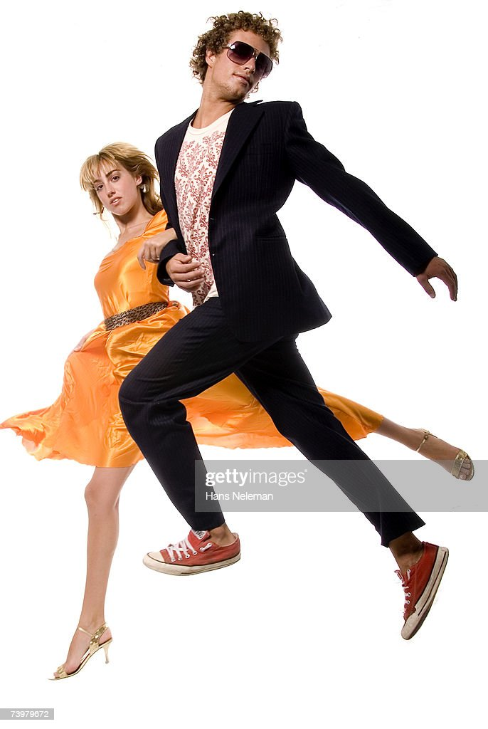 Young couple in alternative evening wear skipping in air : Stock Photo