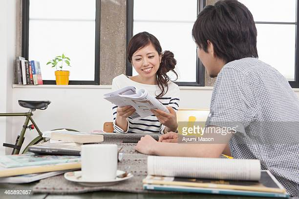 Young couple in apartment planning at table