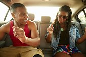 Young couple in back seat of car showing off dance moves