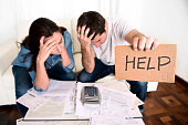 young couple worried in need of money asking for help in cardboard text message sitting in stress at home living room couch accounting debt bills bank , documents , receipts and payments feeling despe