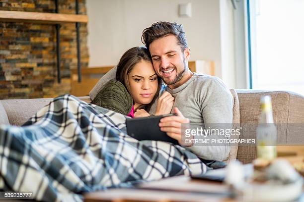 Jeune couple au lit se divertir avec tablette