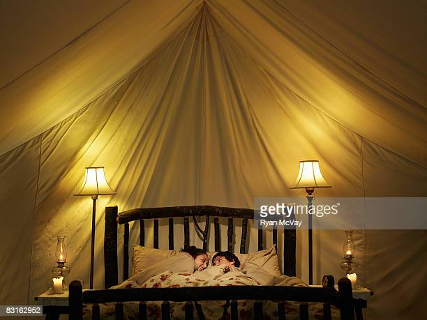 Young couple in bed inside tent.