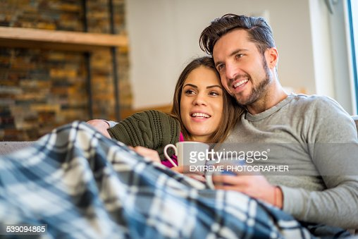 Young couple in bed with hot beverages