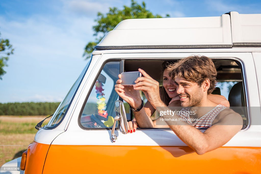 Young Couple In Camper Taking Pictures