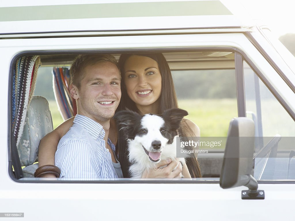 Young couple in camper van with dog. : Stock Photo