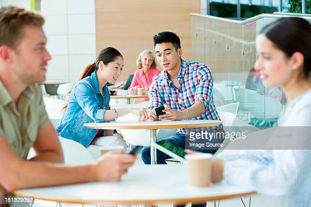 Young couple in canteen area, looking at cellphone