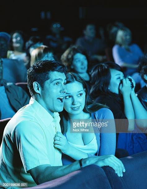 Young couple in cinema reacting to film, close-up