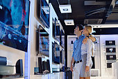 Young couple in consumer electronics store looking at latest laptop, television and photo camera to buy lcd flat tv